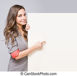 Young brunette pointing at empty billboard. - Portrait of...
