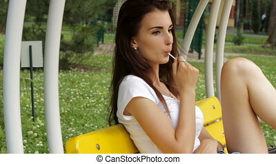 young brunette sits on the bench swings and licks a lollipop