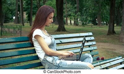 young brunette sitting on a bench in the Park and prints on a laptop