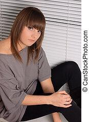 brunette sitting on the window