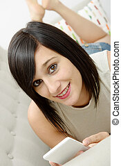 young brunette student lying on the couch with phone