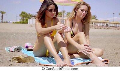 Young brunette sunbathing besides her friend