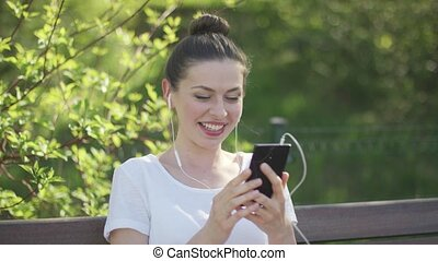 Young brunette talking by smartphone - Smiling attractive...