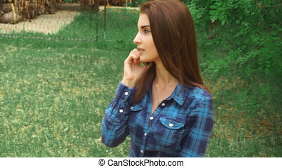 young brunette talking on the phone in the Park