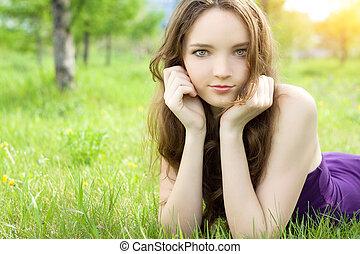 young brunette teenager girl lying on meadow