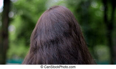 young brunette walking down the street and improves hand hair closeup