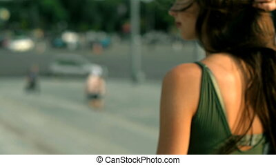 young brunette walking down the street on a sunny day