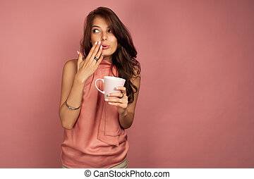 Young brunette wants to tell a secret while drinking tea or coffee