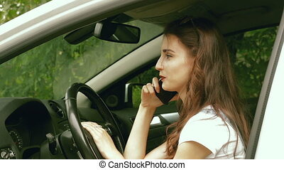 young brunette while driving in the car talking on the phone