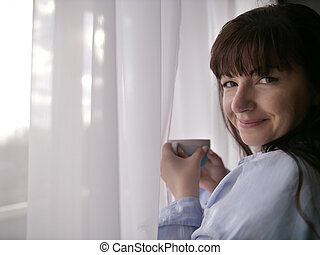 Young brunette with a cup of coffee by the window looking into the camera