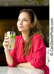 Young brunette with cool refreshment. - Portrait of a young ...