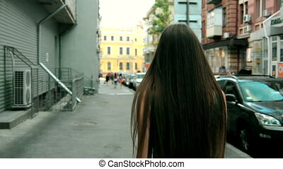 young brunette with long straight hair comes down the street