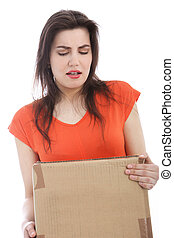 Young brunette woman carrying a heavy cardboard box
