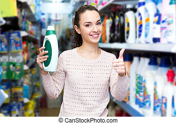 Young brunette woman choosing detergent