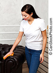 Young brunette woman cleaning dark brown chester leather sofa with microfiber rag in hand