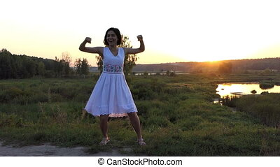 Young Brunette Woman Dances Disco Happily on a Lake Bank at Sunset in Slo-Mo