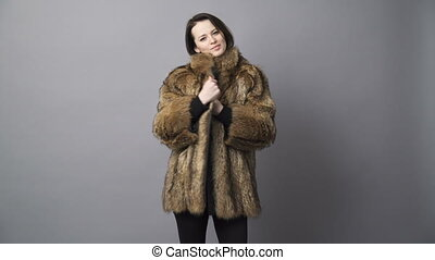 Young brunette woman demonstrating fur coat