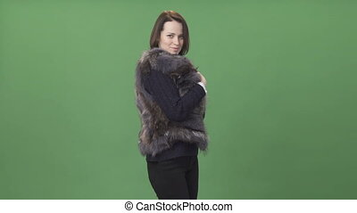 Young brunette woman demonstrating fur vest