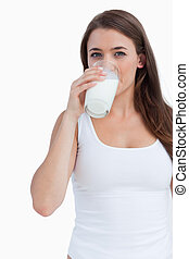 Young brunette woman drinking a glass of milk