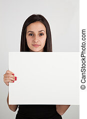 Young brunette woman holding a blank sign