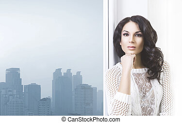 Young brunette woman in a beautiful interior