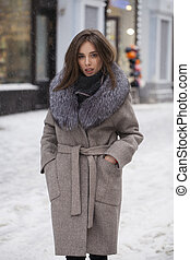 Young brunette woman in a gray coat with a fur collar