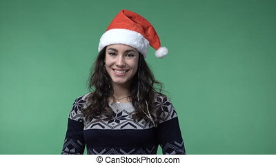brunette woman in a red santa's cap smiling