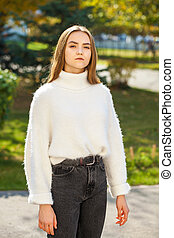 Young brunette woman in a woolen sweater and black jeans