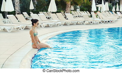 young brunette woman in bikini and sunglasses sitting on tedge of pool and makes splash in Sunny summer day