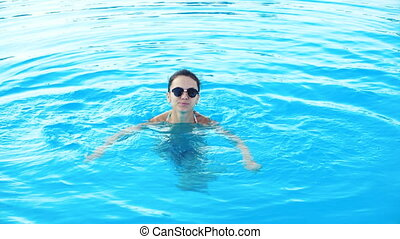 young brunette woman in bikini and sunglasses swims in pool on Sunny summer day