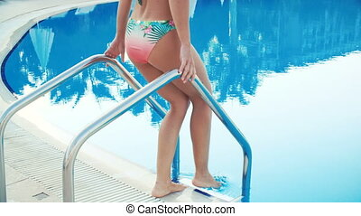 young brunette woman in bikini and sunglasses walks into swimming pool and swims on Sunny summer day