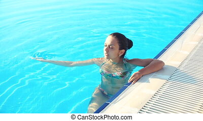 young brunette woman in bikini in pool on a Sunny summer day
