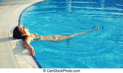young brunette woman in bikini in pool on a Sunny summer day...