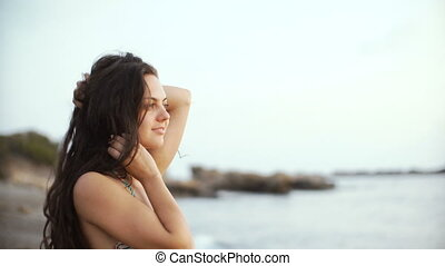 young brunette woman in bikini looking into distance and dreaming on sea background