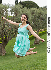 young brunette woman in dress jumping at the outdoors