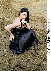 Young brunette woman in elegant black dress