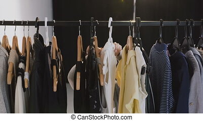 Young brunette woman in glasses looking through a rail of clothing on hangers. Young caucasian woman choosing clothes on a rack in a showroom