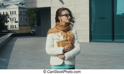 young brunette woman in glasses with books in hands