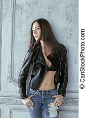 young brunette woman in leather jacket at vintage wall, old interior