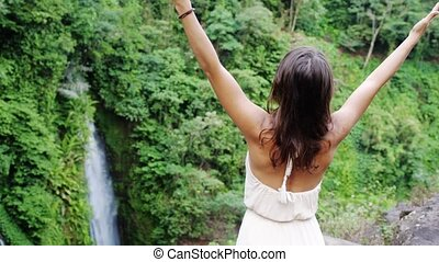 Young brunette woman in long dress rises hands at waterfall in jungle Koh Samui. Thailand. slow motion.