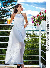 Young brunette woman in long white dress