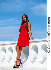 Young brunette woman in red dress