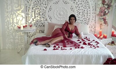 Young brunette woman in red lingerie posing at bed with tray...