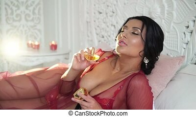 Young brunette woman in red lingerie using perfume...