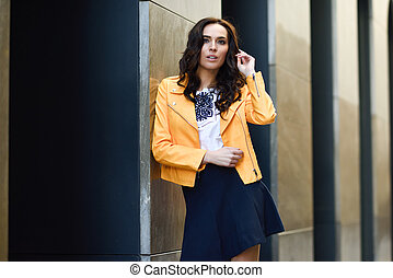 Young brunette woman in urban background.