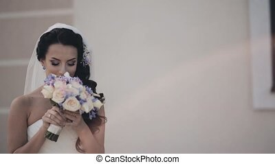 Young brunette woman in wedding dress standing outside and smelling the bouquet. Beautiful bride before wedding ceremony