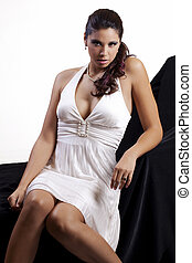 Young brunette woman in white dress sitting