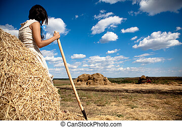 Young brunette woman in white dress standing backwards with hay pitchfork