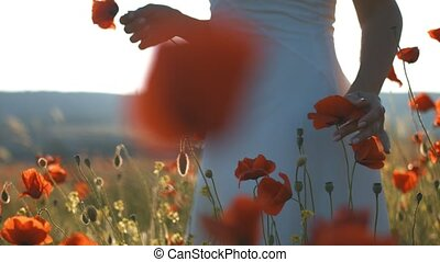 Young brunette woman in white sundress walking through poppies field at sunset