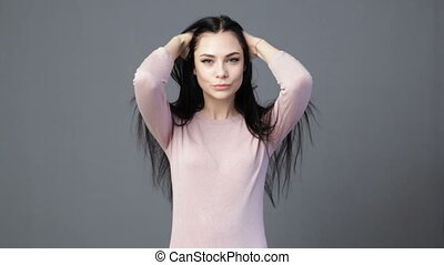 Young brunette woman is touching the hair